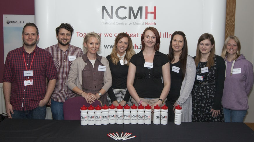NCMH pop up banner with team stood infront, and branded waterbottles infront of them