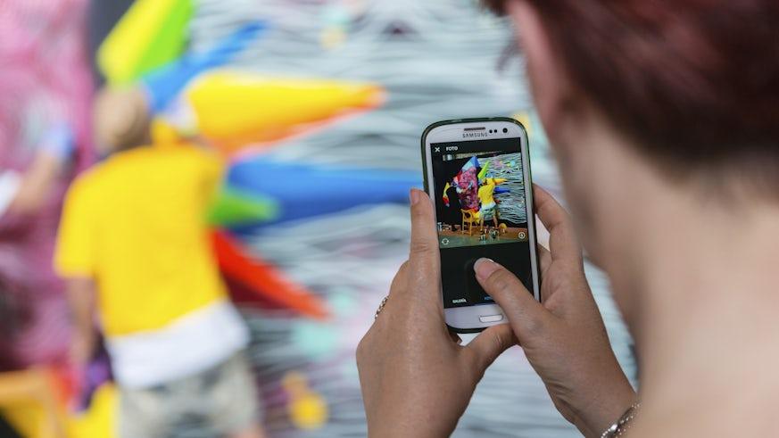 Woman looking through mobile phone at graffiti