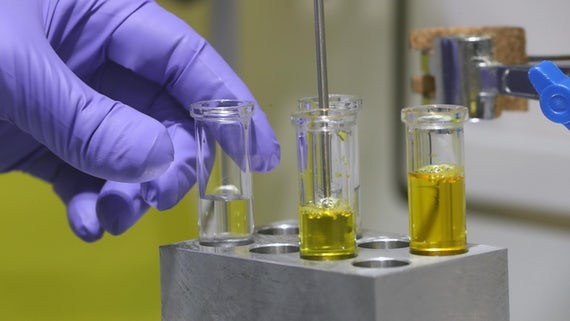 Gloves hand adjusting test tubes with yellow chemical