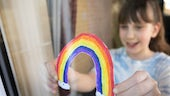 Child sticking rainbow on window stock image
