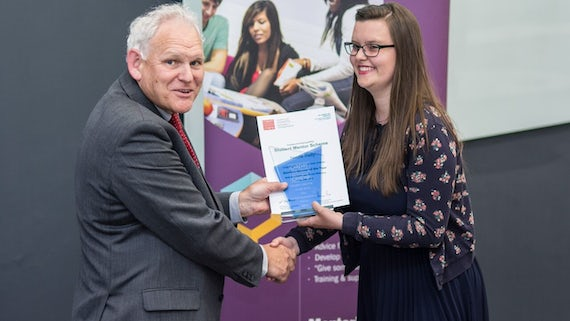 Nicole Riley receiving her trophy at the Student Mentor Celebration event
