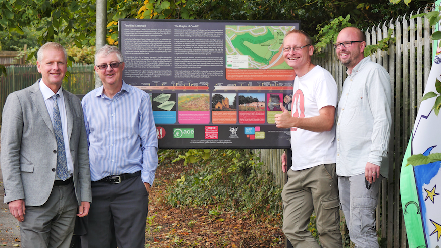 Staff and stakeholders around information sign
