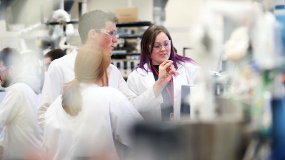 Woman with purple hair and man in science lab on campus