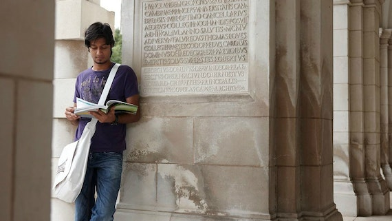 Male student wearing a purple T-shirt stands next to a building reading a book.