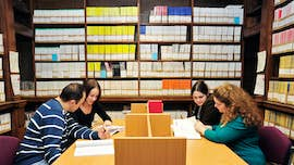 Students working surrounded by journals in the library.