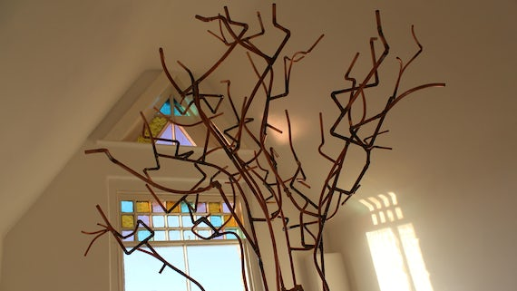 Growth by Susan Adams, a tree-like structure made from copper pipes