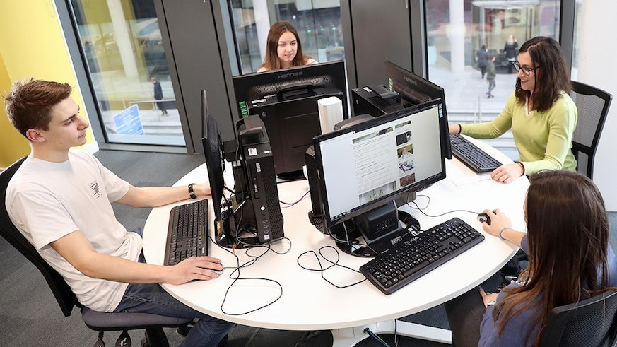 Four students sit around a table, each is working at a computer