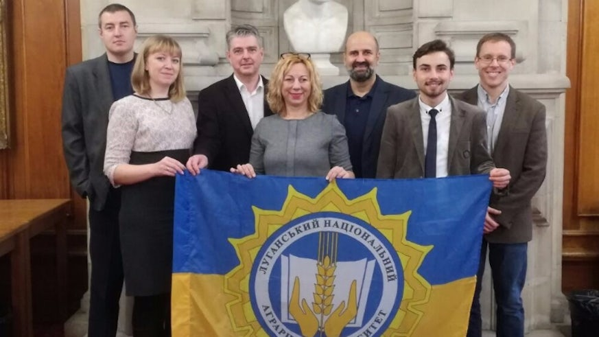 Image shows a group of five men and two women posing with the Ukrainian flag
