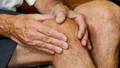 Man clutching leg in great pain