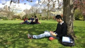 Pg students sitting on the grass and reading books