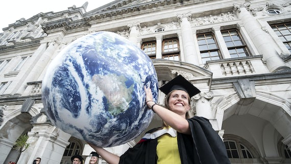 Earth and Ocean Science graduate with globe