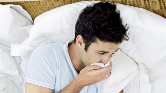 Man with cold in bed