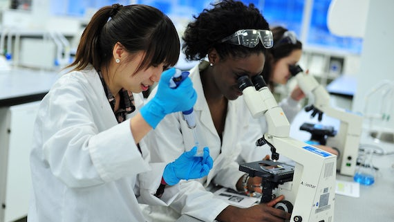 Three female students in white coats, working in a laboratory