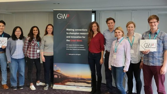 9 young men and women standing by a pull up stand to show their collaboration as a GW4 group.