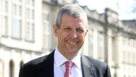 Man in suit smiles outside University buildings