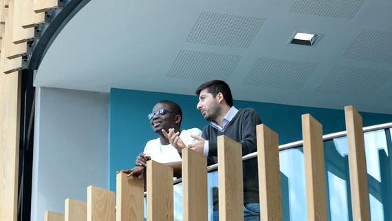 Two male postgraduate students leaning over balcony