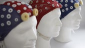 Three white mannequin heads with colourful blue and red EEG caps with places for electrodes to be fitted