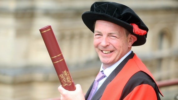 Marcus McGilvray in graduation robes