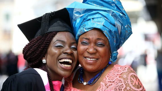 Female student graduating with mother in traditional headdress