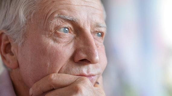 Elderly man resting with his hand on his chin