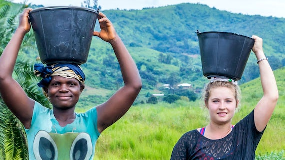 Two women standing outside with holding buckets on their heads.