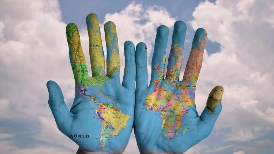 world map drawn on hands