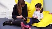 Photograph of child sat on the floor doing an activity with a psychologist