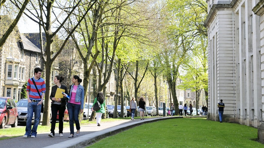 Students walking along Park Place in the middle of the Cathays Park campus.