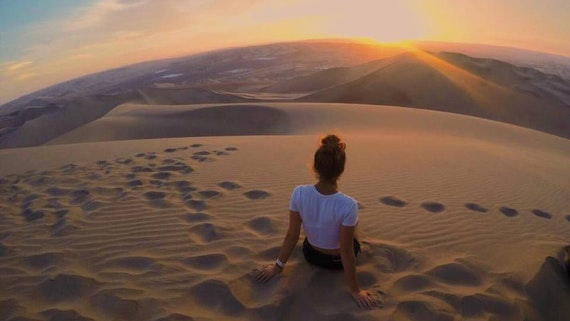 A woman sits on a sand dune watching a sunset