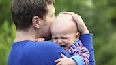 Father consoling crying child