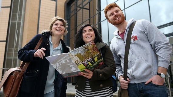 Three PG students standing outside. One of them is holding a Cardiff University postgraduate brochure.