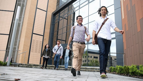 Two male PG students walking out of a building