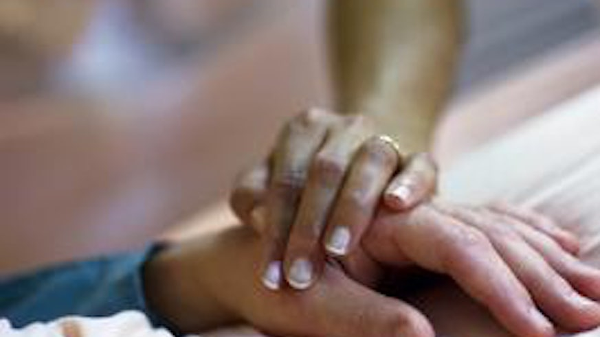 A nurse's hand on a patient's hand
