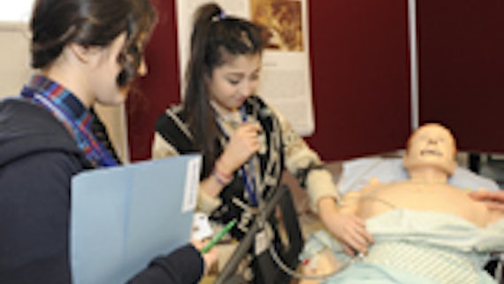 A pupil being shown how to monitor patients' vital signs