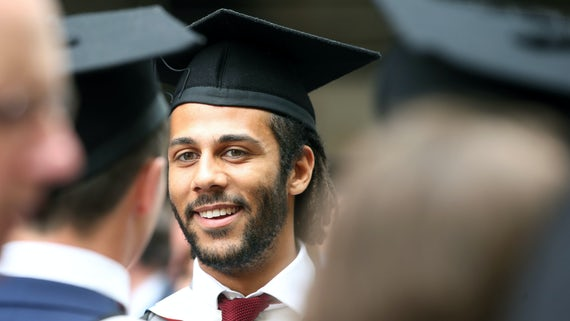 Close-up of male graduand in a cap and gown standing in a crowd.