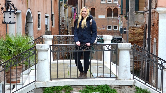 A woman stands upon a small footbridge in Venice