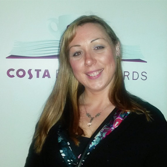 Image of a woman standing in front a wall with 'Costa Book Awards' displayed in red letters.