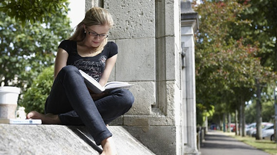 Female student sitting on a wall and reading a book.