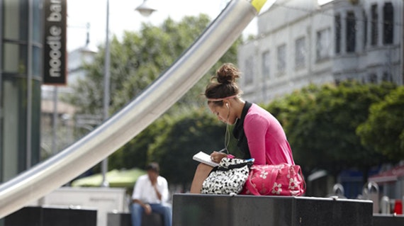 Female student reading a book in Cardiff city centre.