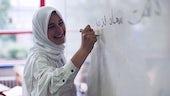 Woman in headscarf writing on white board