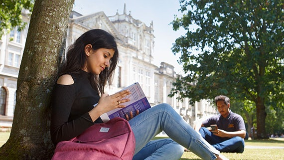 Students sat reading outside Main Building