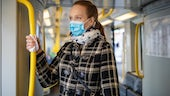 Stock image of woman in a mask on public transport