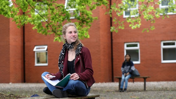 Female undergraduate student sitting on bench smiling, outside a redbrick building under green leafed trees