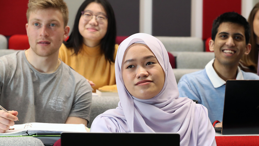Image of four students, two males and two females sat in a lecture theatre. Female in front row is wearing a headscarf.