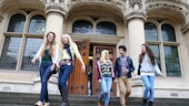 Undergraduate students outside Queen's Buildings
